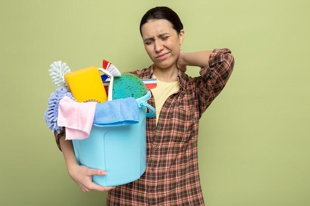 Junge putzfrau im karierten hemd, die einen eimer mit reinigungswerkzeugen hält, die unwohl müde und erschöpft aussieht, indem sie ihren nacken berührt und schmerzen auf grün fühlt