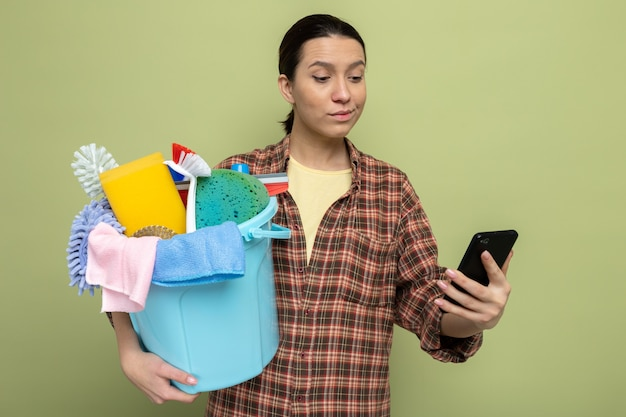 Junge putzfrau im karierten hemd, die einen eimer mit reinigungswerkzeugen hält und ihr handy mit einem lächeln im gesicht auf grün betrachtet