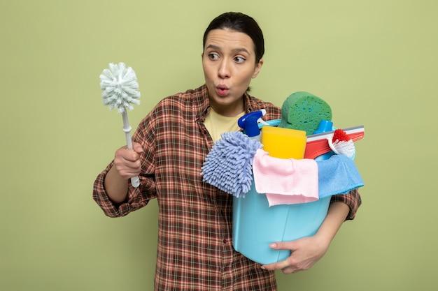 Junge putzfrau im karierten hemd, die reinigungsbürste und eimer mit reinigungswerkzeugen hält, die die bürste verwirrt auf grün betrachten