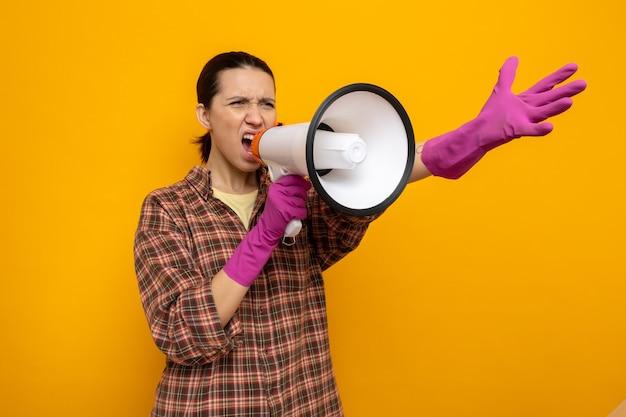 Junge putzfrau im karierten hemd in gummihandschuhen, die emotional und aufgeregt mit erhobenem arm über orangefarbener wand zum megaphon schreit