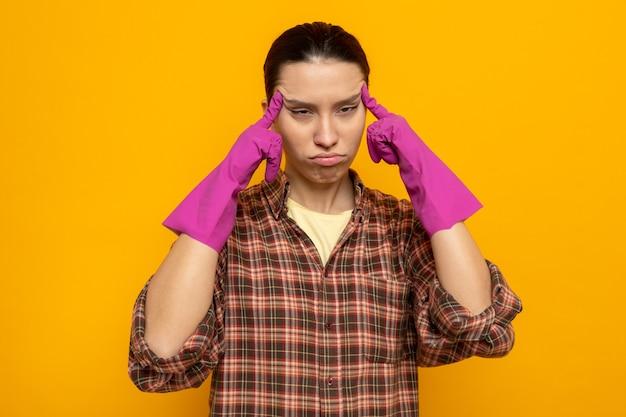 Junge putzfrau im karierten hemd in gummihandschuhen, die ihre schläfen berührt, sieht unwohl, müde und erschöpft über oranger wand stehend aus