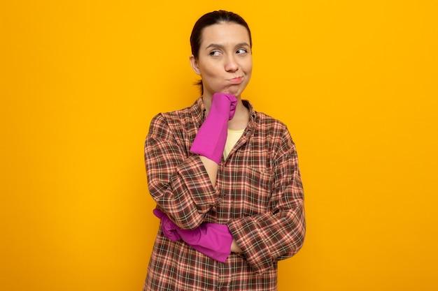 Junge putzfrau im karierten hemd in gummihandschuhen, die mit der hand am kinn mit nachdenklichem ausdrucksdenken beiseite schaut