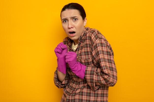 Junge putzfrau im karierten hemd in gummihandschuhen hat angst, die hände zusammenzuhalten, die auf orange stehen