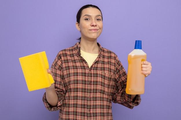 Junge putzfrau in freizeitkleidung, die eine flasche reinigungsmittel mit schwamm hält und nach vorne schaut, glücklich und positiv lächelt zuversichtlich über lila wand
