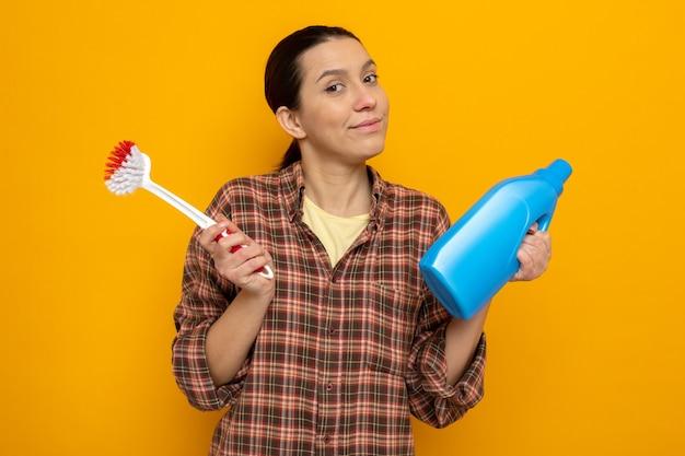 Junge putzfrau in freizeitkleidung, die eine reinigungsbürste und eine flasche reinigungsmittel mit skeptischem lächeln auf dem gesicht über der orangefarbenen wand hält