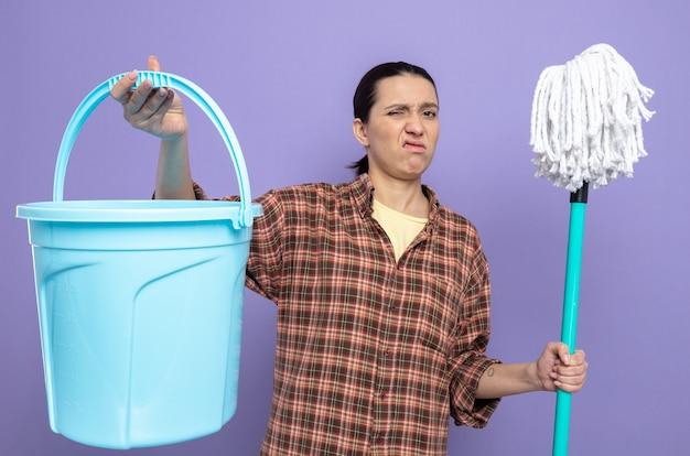 Junge putzfrau in freizeitkleidung, die mopp und eimer hält, unzufrieden mit skeptischem ausdruck, der auf lila steht