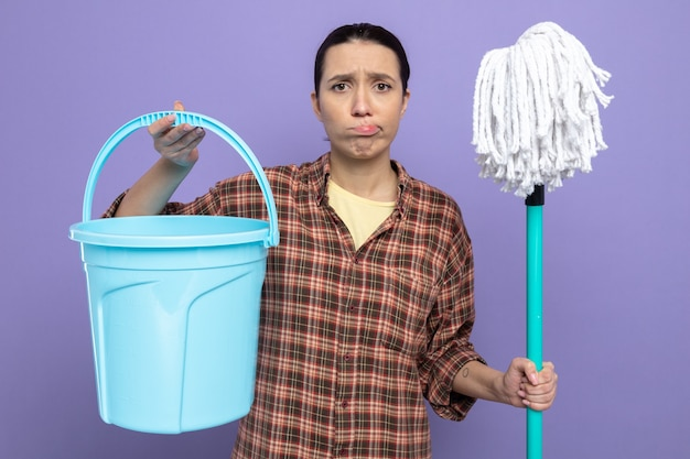 Junge putzfrau in freizeitkleidung, die mopp und eimer verwirrt und sehr enttäuscht hält und einen schiefen mund über der lila wand steht?