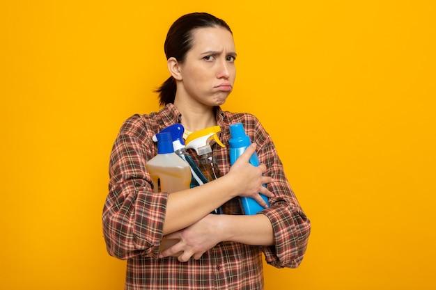 Junge putzfrau in freizeitkleidung, die putzutensilien hält und mit gerunzelter stirn über oranger wand steht