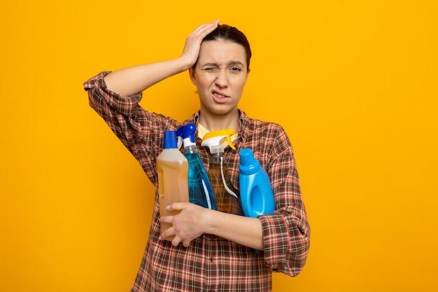Junge putzfrau in freizeitkleidung, die reinigungsmittel hält, die mit der hand auf dem kopf verwirrt aussieht, weil sie auf orange steht