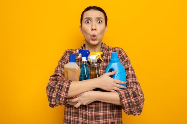 Junge putzfrau in freizeitkleidung, die reinigungsmittel hält und besorgt und überrascht aussieht
