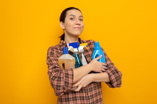 Junge putzfrau in freizeitkleidung, die reinigungsmittel hält und fröhlich auf orange lächelt