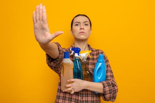 Junge putzfrau in freizeitkleidung, die reinigungsmittel mit ernstem gesicht hält, die stoppgeste mit der hand auf orange macht