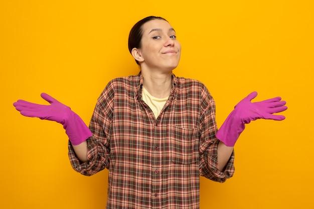 Junge putzfrau in freizeitkleidung in gummihandschuhen, die lächelnd die arme zu den seiten ausbreitet, die auf orange stehen