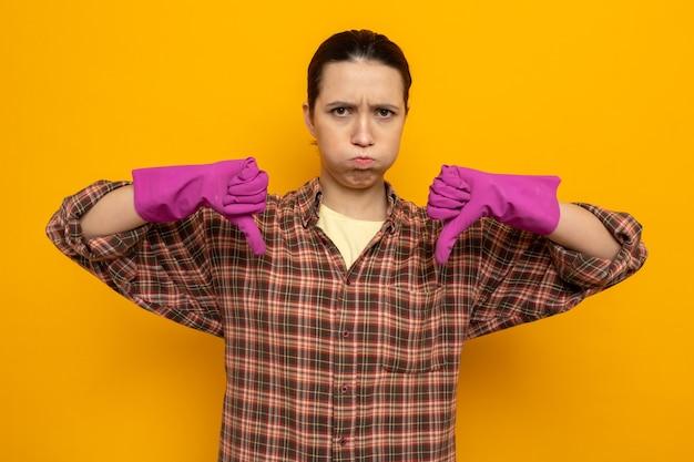 Junge putzfrau in freizeitkleidung in gummihandschuhen, die mit stirnrunzelndem gesicht nach vorne schaut und daumen nach unten über oranger wand steht