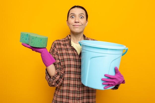 Junge putzfrau in freizeitkleidung in gummihandschuhen, die schwamm und eimer hält und nach vorne schaut, erstaunt und überrascht, über orangefarbener wand zu stehen