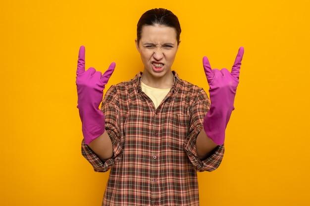 Junge putzfrau in freizeitkleidung in gummihandschuhen sieht selbstbewusst aus und zeigt rocksymbol
