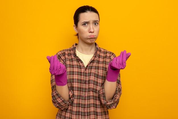 Junge putzfrau in freizeitkleidung in gummihandschuhen verärgert wehende wangen, die sich die finger reiben, die über oranger wand stehen