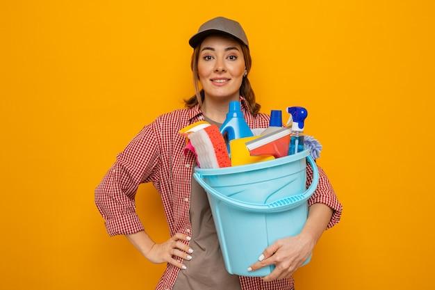 Junge putzfrau in kariertem hemd und mütze, die einen eimer mit reinigungswerkzeugen hält und die kamera mit einem lächeln im gesicht ansieht, bereit für die reinigung auf orangefarbenem hintergrund