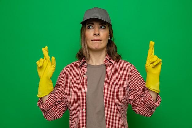 Junge putzfrau in kariertem hemd und mütze mit gummihandschuhen, die nach oben schauen und den wünschenswerten wunsch machen, die daumen zu drücken