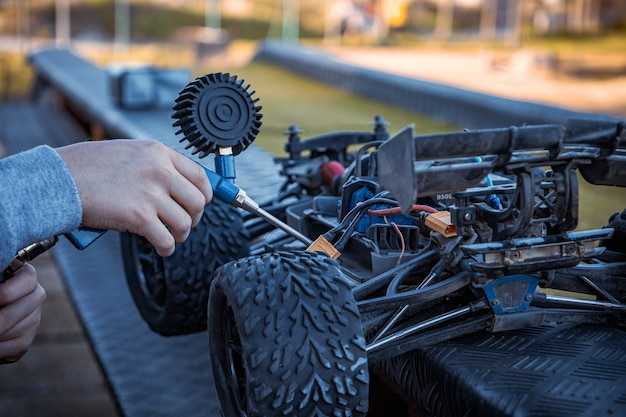 Junge putzt sein rc-auto mit einem luftkompressor