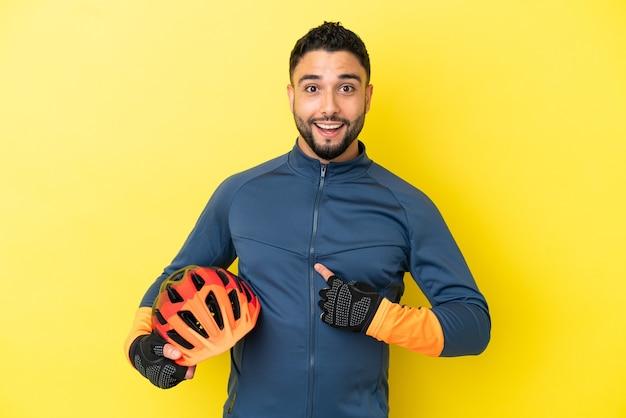 Junge radfahrer arabischer mann isoliert auf gelbem hintergrund mit überraschtem gesichtsausdruck