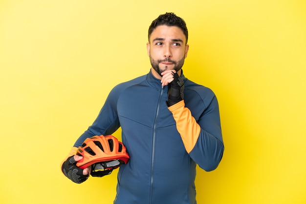 Junge radfahrer arabischer mann isoliert auf gelbem hintergrund mit zweifeln und denken