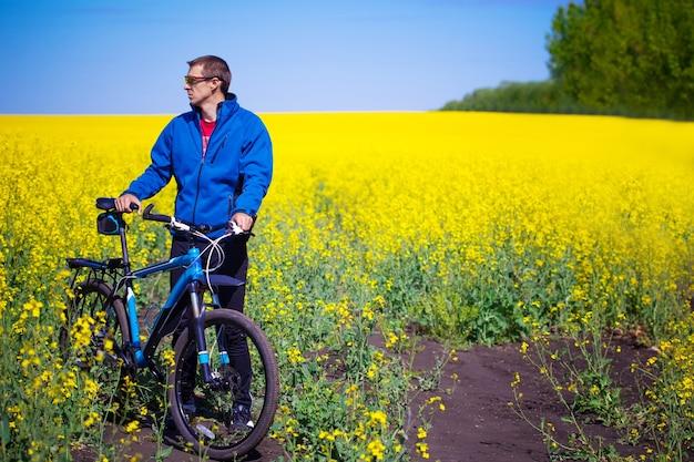 Junge radfahrer fährt im frühjahr rapsfeld mit dem mountainbike