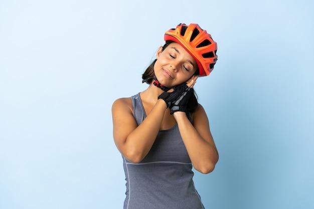 Junge radfahrerfrau auf blau, die schlafgeste im liebenswerten ausdruck macht