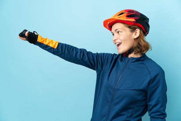 Junge radfahrerfrau lokalisiert auf blauem hintergrund, der eine daumen hoch geste gibt