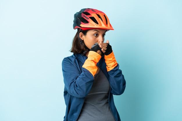 Junge radfahrerfrau lokalisiert auf blauem hintergrund, der mund bedeckt und zur seite schaut