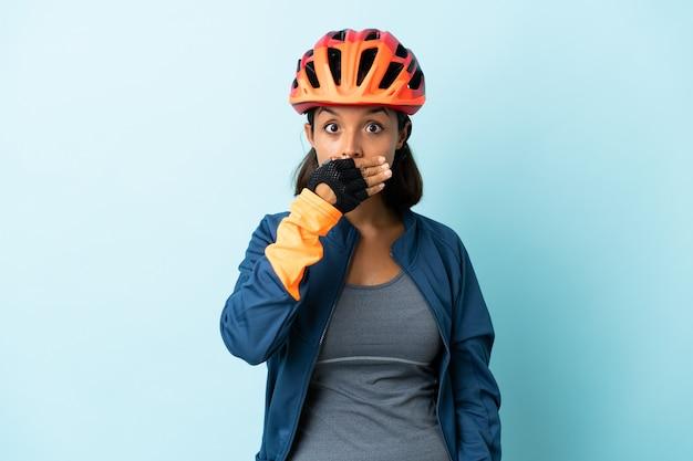 Junge radfahrerfrau lokalisiert auf blauem hintergrund, der mund mit hand bedeckt
