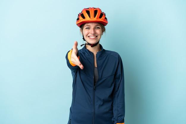Junge radfahrerfrau lokalisiert auf blauem hintergrund händeschütteln für das schließen eines guten geschäfts