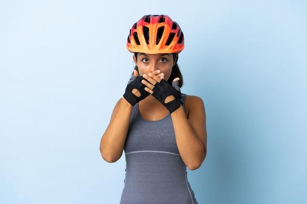 Junge radfahrerfrau lokalisiert auf blauem kegelmund mit den händen