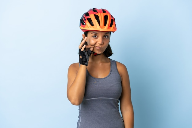 Junge radfahrerfrau lokalisiert auf blauer wand, die ein zeichen der stille geste zeigt