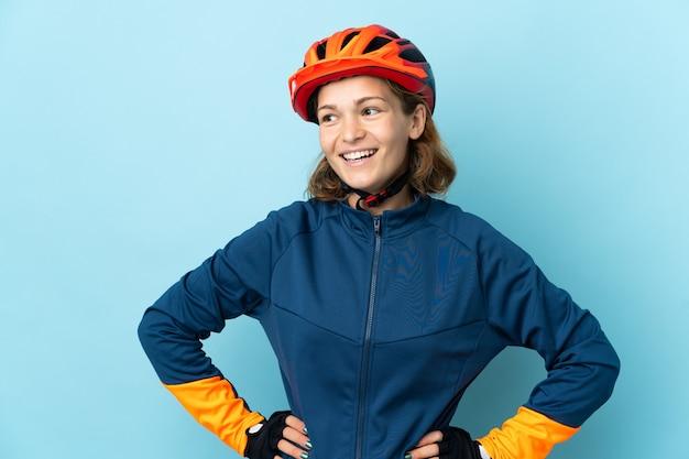Junge radfahrerfrau lokalisiert auf blauer wand, die mit armen an der hüfte aufwirft und lächelt
