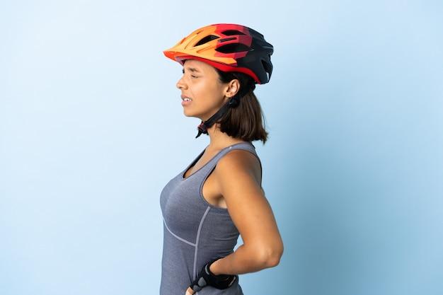 Junge radfahrerin auf blau, die unter rückenschmerzen leidet, weil sie sich bemüht hat