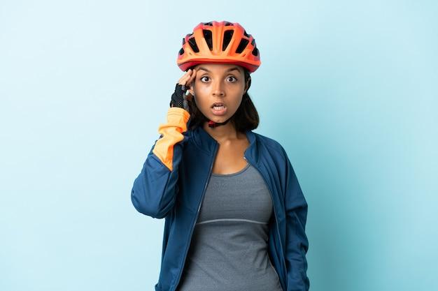 Junge radfahrerin auf blau isoliert hat etwas erkannt und beabsichtigt die lösung