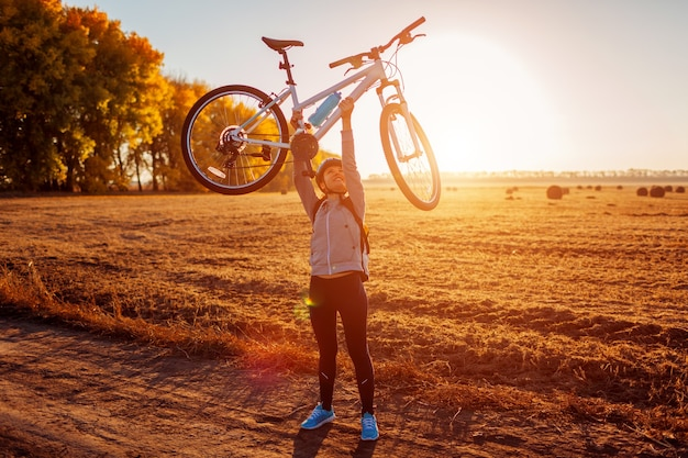 Junge radfahrerin, die bei sonnenuntergang ihr fahrrad im herbstfeld anhebt. glückliche frau feiert erfolg mit fahrrad in händen.