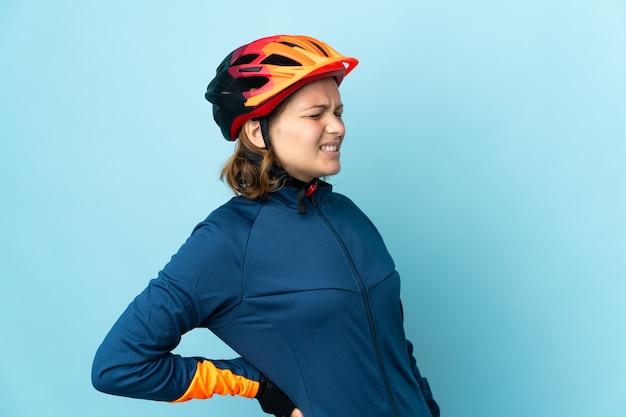 Junge radfahrerin isoliert auf blauer wand, die unter rückenschmerzen leidet, weil sie sich bemüht hat