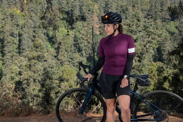 Junge radfahrerin posiert mit ihrem fahrrad an einem aussichtspunkt mit einer bewaldeten landschaft im hintergrund