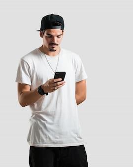 Junge rappermannnahaufnahme der hand ein mobile, unter verwendung des internets und der sozialen netzwerke, des positiven gefühls der zukunft und der modernität berührend