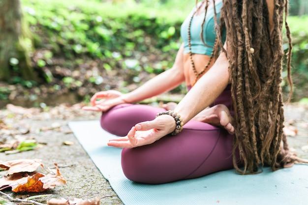 Junge rastafrau, die yoga (lotoshaltung) im park auf einer matte tut