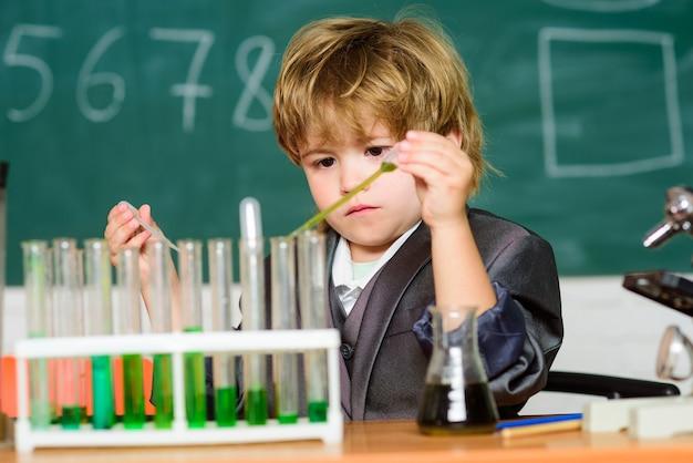 Junge reagenzgläser flüssigkeiten chemie. chemische analyse. talentierter wissenschaftler. kind studiert chemie. biotechnologie und pharmazie. genialer schüler. bildungskonzept. wunderkind experimentiert mit chemie.