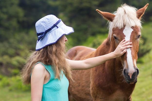 Junge recht blonde langhaarige frau im sonnenhut schönes kastanienpferd auf unscharfem grünem sonnigem sommer streichelnd. liebe zum tier, pflege, freundschaft, treue und landwirtschaftskonzept.