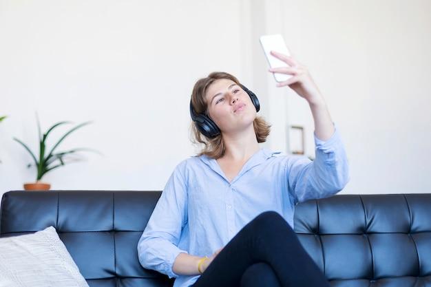 Junge recht lange haarfrau, die auf einem sofa macht selfie an ihrem telefon sitzt