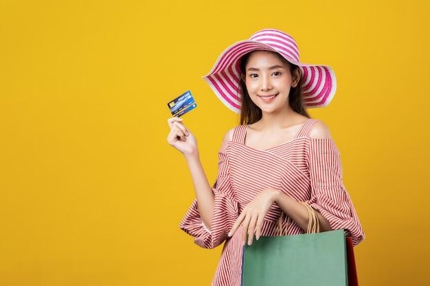 Junge recht nette asiatin, die im sommerartkostüm hält kreditkarte und einkaufstaschen mit dem smileygesicht steht im studio trägt.