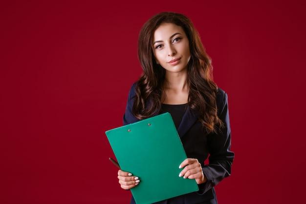 Junge regisseurin, gekleidet in formellen anzug, hält dokumente und lächelt auf einem roten. unternehmenskonzept. steuerung.