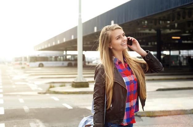 Junge reisefrau, die am handy geht und spricht