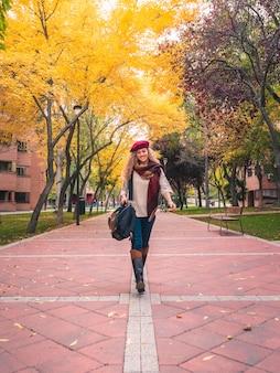 Junge reisefrau in der herbstausstattung lächelnd, hübsche herbstfarben betrachtend