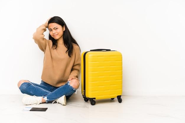 Junge reisende frau, die auf dem boden mit einem koffer sitzt, isoliert müde und sehr schläfrig, hand auf kopf haltend